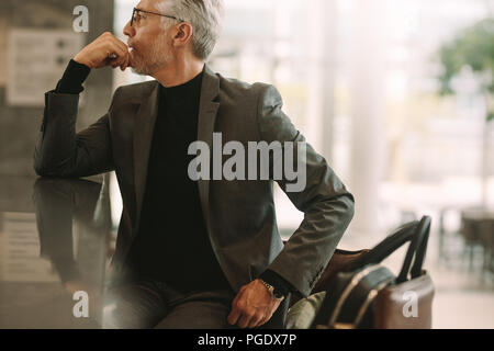 Portrait of senior businessman sitting at cafe. Senior man in business suit looking away while sitting at coffee shop. - Stock Photo