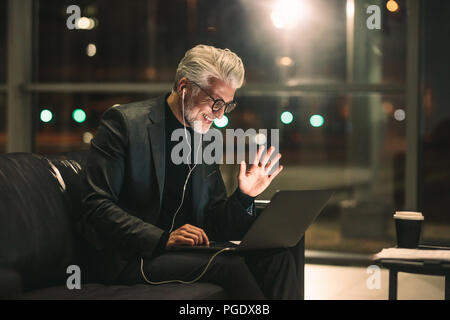 Middle aged man on video call using a laptop in office lobby. Smiling businessman late at night in office making gestures on a video call. - Stock Photo