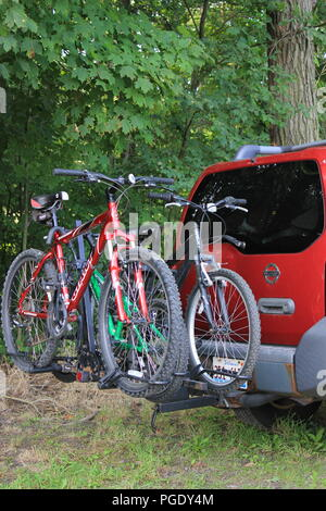 #summerfun Summer fun Red SUV holding two bicycles on the bicycle storage rack trunk at the Blueberry Patch in Sawyer, Michigan, USA on a hot summer day. - Stock Photo