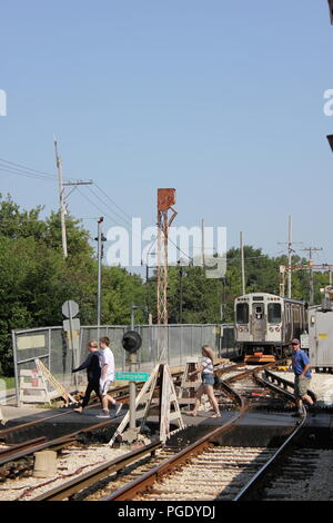Pedestrians crossing the railroad tracks at the CTA Yellow Line Skokie Swift Dempster Street Station. - Stock Photo