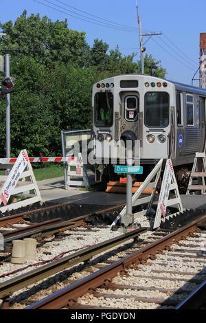 CTA Yellow Line Skokie Swift commuter train rolling into the Dempster Street Station. - Stock Photo