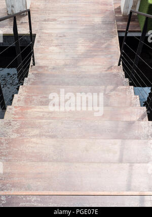 Modern wooden staircase is over the small pond to the wooden floor in the urban park. - Stock Photo