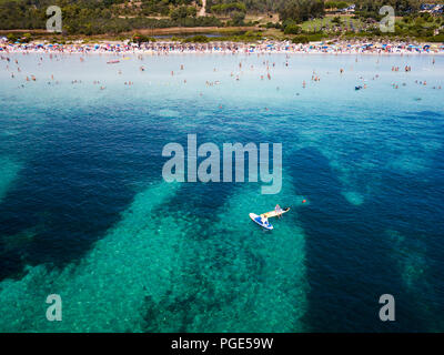 Aerial view of two people doing stand up paddleboarding (SUP) on a beautiful turquoise sea. Beautiful white beach with relaxed people on background.   - Stock Photo