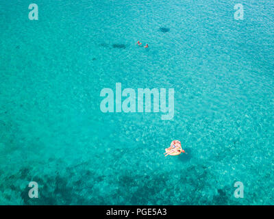 Aerial view of two people relaxed on an inflatable mat floating on a beautiful turquoise sea. Cala Brandinchi, Sardinia, Italy. - Stock Photo
