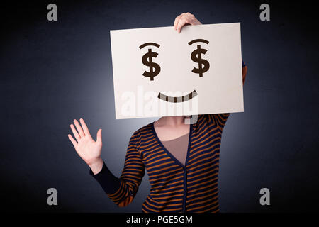 Young casual woman hiding behind a greedy face drawing on cardboard - Stock Photo