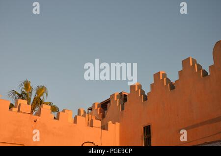 Oriental architecture in Marrakech, Morocco, before sunset, orange, stone walls, palm trees, vacation, sky, sunny, bright, traditional, souk, market - Stock Photo