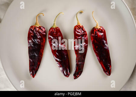 Four guajillo chilies on a tan plate against a fabric background, shot flat-lay - Stock Photo