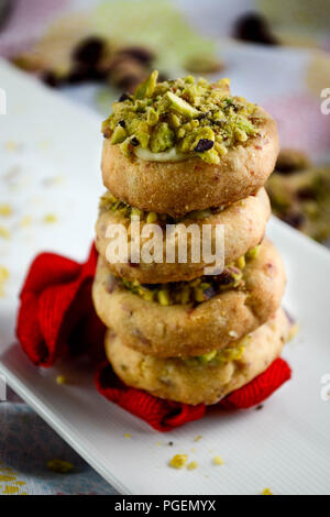Miniature cranberry shortbread cookies with white chocolate and pistachios served on a plate and decorated with a red ribbon - Stock Photo