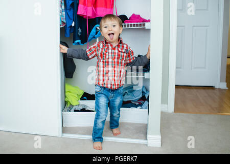 Candid natural portrait of funny cute white Caucasian little boy toddler in wardrobe at home making funny face showing tongue, lifestyle documentary s - Stock Photo