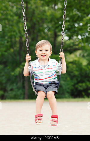 Portrait of happy smiling little boy toddler in tshirt and jeans shorts on swing on backyard playground outside on summer day, happy childhood lifesty - Stock Photo
