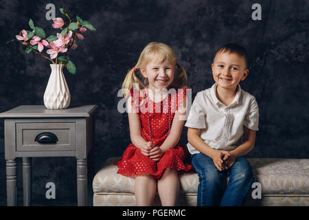 Group portrait of two white Caucasian prescholler boy and girl sitting together on couch indoors. Children smiling laughing together, friendship and h - Stock Photo