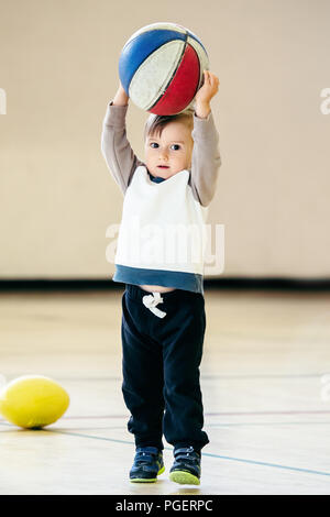 Cute adorable little small white Caucasian child toddler boy playing with ball basketball in gym on plain white light background, having fun, healthy  - Stock Photo