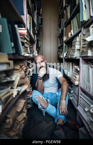 Upset hipster man sitting on floor in library. depression concept