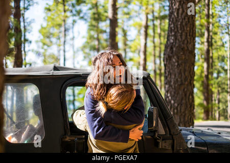 happiness during outdoor leisure activity for caucasian young couple in love and friendship. the woman hug the man laughing a lot and enjoying the lif - Stock Photo