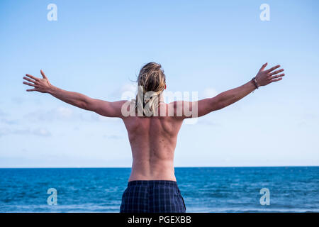 beautiful young man viewed from rear with open arms in front of the ocean and freedom. success and enjoyment concept for young people in summer vacati - Stock Photo