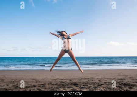 beautiful body fitness lifestyle young woman jump full of happiness at the beach near the shore and the waves of the blue ocean. joyful and summer fun - Stock Photo