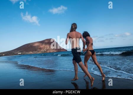couple of young man and woman running on the beach near thw ocean. outdoor leisure activity for happy couple of traveler during summer holiday. beauti - Stock Photo