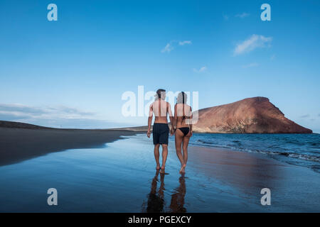 romantic couple of young beautiful man and woman walking on the shore at the beach in bikini and swimwear. looking eachother with love and relationshi - Stock Photo
