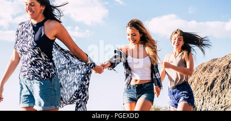 three cheerful attractive young females friends walk together taking hands with blue sky and mountain in background. freedom and happiness enjoying th - Stock Photo