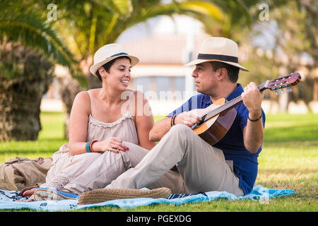 nice happy alternative couple enjoy the outdoor leisure activity together with love and fun playing an acoustic guitar and singing some songs. sitting - Stock Photo
