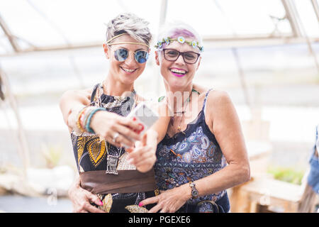 hippy couple of caucasian beautiful females use a smart phone. Different ages  nice attractive people stay together in happy leisure activity with fri - Stock Photo