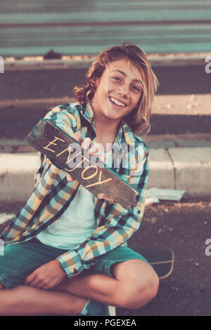 young beautiful male teenager take a piece of wood wht enjoy written on it. positive vibes word for all the people. hand made painted. happy and peace - Stock Photo