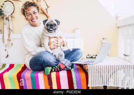 total happiness for beautiful cheerful caucasian young woman hugged with her best friends fat dog pug smiling too. friendship at home and enjoy lifest - Stock Photo