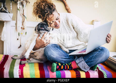 real best friends cheerful woman working at laptop on the terrace at home while hug her best love and friends  smiling dog pug sitting at his left. co - Stock Photo