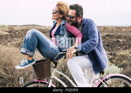 happy adult caucasian, couple having fun with bicycle in outdoor leisure activity. concept of active playful people with bike during vacation - everyd - Stock Photo