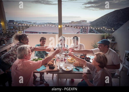 group of different ages people in friendship eat together a dinner event cheering with wine and enjoy the lifestyle. happiness and joyful for friends  - Stock Photo