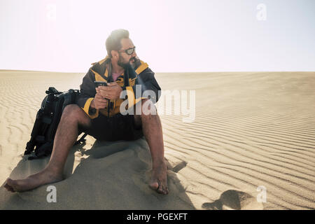 lonely caucasian middle age man travel barefoot in the desrt with backpack and phone and tripod to take pictures. alternative travel vacation concept  - Stock Photo