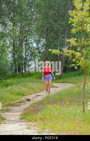 Woman walking the Camino de Santiago through wild flowers in woodland along the banks of the river rio Ucieza near Villalcazarde Sirga Spain - Stock Photo
