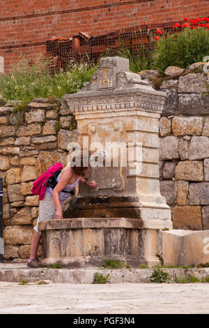 Women Pilgrim taking a drink of water from a fountain  while walking the Camino  de Santiago the way of St James at Castrojeriz Spain - Stock Photo