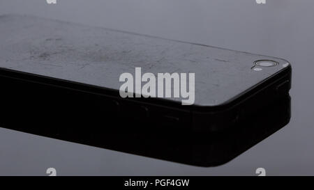 Old smartphone that the film has scratched.on black background - Stock Photo
