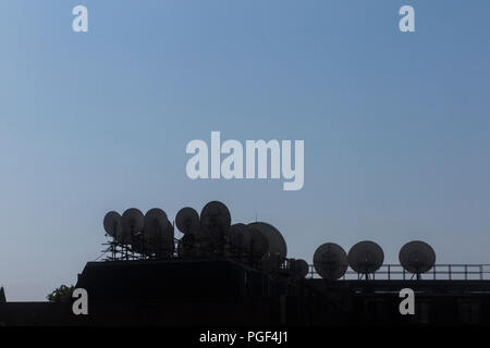 Lots of satellite dishes in London silhouetted against a blue sky - Stock Photo