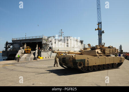 Soldiers assigned to Bravo Company Team, 2nd Battalion, 5th Cavalry Regiment, 1st Armored Brigade Combat Team, 1st Cavalry Division offload an M1A2 Abrams tank from the United States Naval Ship Carson City, an expeditionary fast transport, at the Port of Constanta, Romania, Aug. 20, 2018. The Soldiers are redeploying after Noble Partner 2018, a Georgian Armed Forces and U.S. Army Europe cooperatively-led event improving readiness and interoperability of Georgia, U.S. and participating nations. - Stock Photo