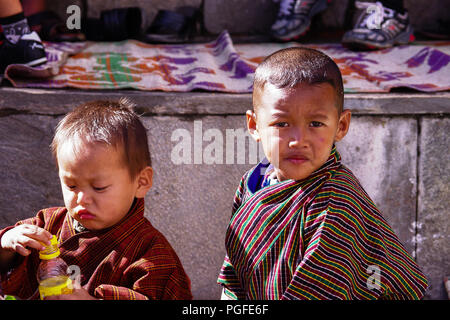Two young boys in traditional costume known as a Gho. Photographed at the colourful Thimpu Tshechu Festival, one of Bhutan's grandest  celebrations - Stock Photo