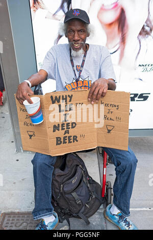 A panhandler on Seventh Avenue in Manhattan with a frank sign saying that donations will be used for beer. - Stock Photo