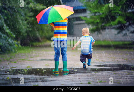 Children walking in wellies in puddle on rainy weather - Stock Photo