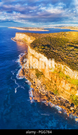 Steep rugged edge of sandstone plateau forming Sydney's north head at the entrance to the Harbour guarding from open pacific ocean with city CBD on ho - Stock Photo