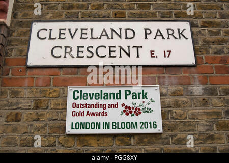 plaque commemorating awards received by cleveland park, walthamstow, at the 2016 london in bloom contest below a cleveland park crescent street sign - Stock Photo