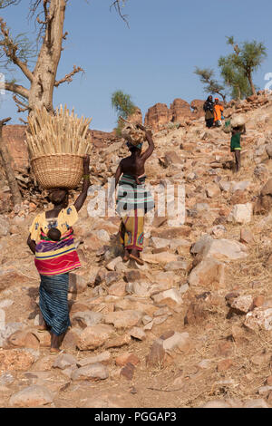 African women carryng babies on their back climb a steep stone path bringing millet and other products to their village in Dogon country, Mali - Stock Photo