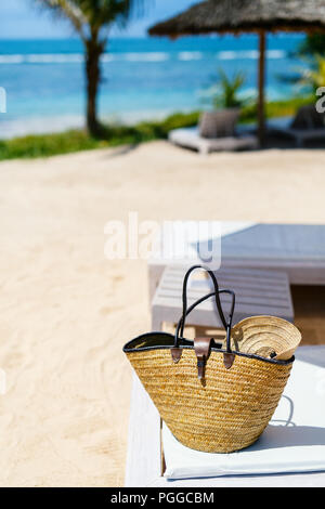 Close up of a straw bag on a tropical beach - Stock Photo