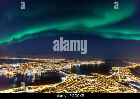 Incredible Northern lights Aurora Borealis activity above town of Tromso in Northern Norway - Stock Photo