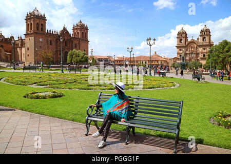 Young female relaxing on a bench at Plaza de Armas with Cusco Cathedral and the Iglesia de la Compania de Jesus in background, Cusco, Peru - Stock Photo