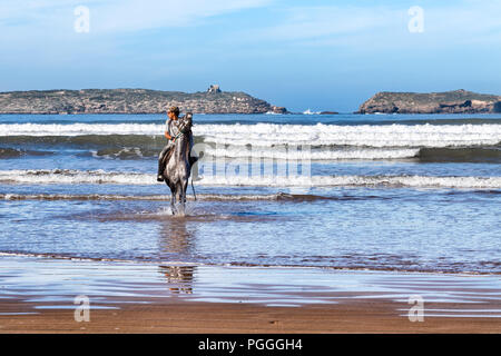 ESSAOUIRA, MOROCCO-DEC 22, 2012: Man riding a horse in the ocean waves at Essaouira, Morocco. Horseback riding is a popular activity on the beach, bot - Stock Photo