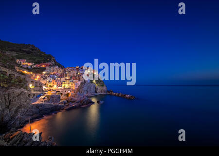 The town of Manarola, with lights on, built upon a cliff above the Mediterranean Sea and one of the five cinque terre villages near La Spezia, Italy. - Stock Photo