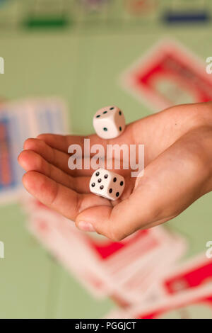 The hand throws game dice on the background of the playing field - Stock Photo
