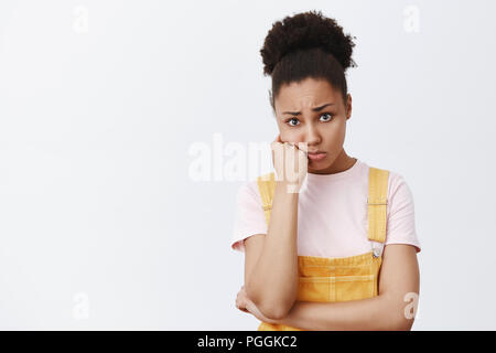 Girl being worried for friend sympathizing her story about breakup. Portrait of gloomy upset good-looking woman in trendy yellow overalls, leaning on fist frowning from sadness over grey wall - Stock Photo