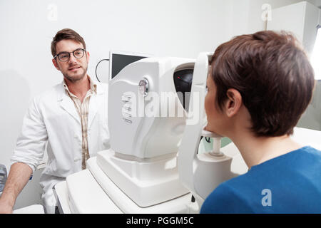 eye Doctor is measuring a patient's visual field with the OCT test /Ophthalmologist in eyes clinic is doing diagnostic vision exam/ concept health and - Stock Photo
